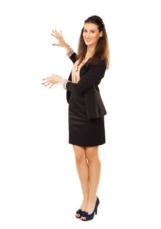 Cheerful corporate woman standing in studio showing copyspace photo