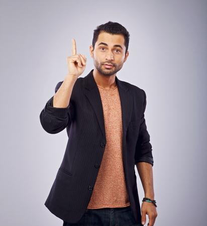 Portrait of a friendly guy pointing upwards