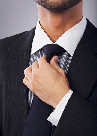 adjust: Closeup of a corporate man adjusting his necktie