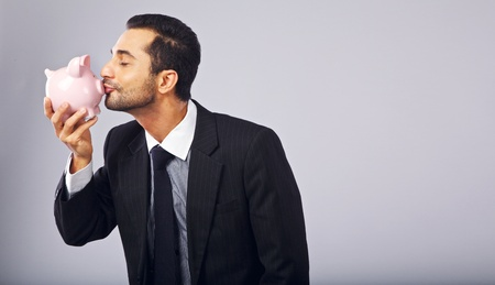 Successful businessman kissing a piggy bank while holding it photo