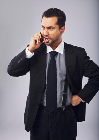 middle eastern ethnicity: Young professional angry with someone over the phone Stock Photo