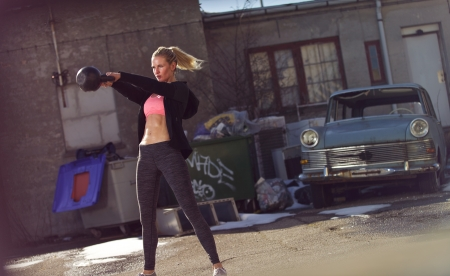determination: Female athlete in a crossfit workout outdoors Stock Photo
