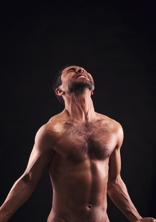 Muscular man on dark background screaming photo