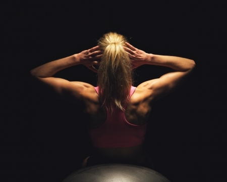 toned: Fitness woman doing stomach crunches while lying on yoga ball