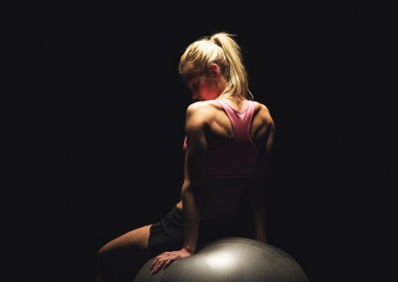 woman sport: Portrait of a fitness woman sitting on a pilates ball and having her workout break Stock Photo