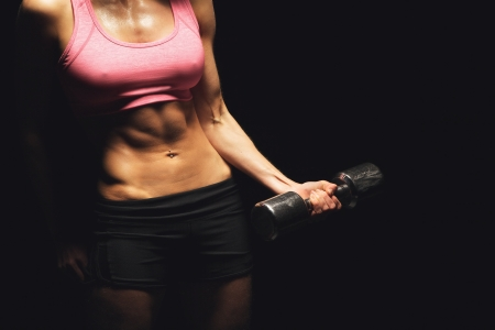flat stomach: Torso of a woman with toned body working out on dark background