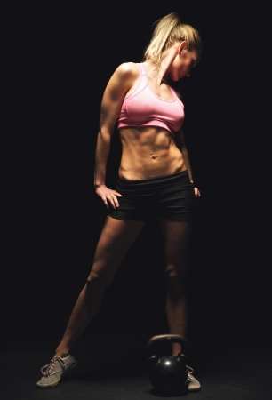 Fitness woman standing and showing off her toned and muscular athletic body photo