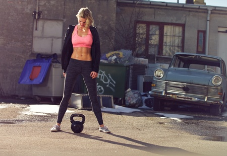Ghetto girl with kettlebell in a crossfit training outdoor photo