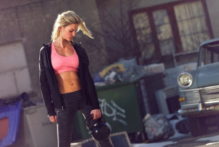 toned: Attractive and athletic woman with kettlebell exercising outdoors
