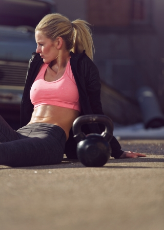 Attractive female sitting on the street and resting after workout photo