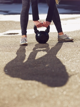 Outdoor fitness woman lifting a heavy kettle bell photo