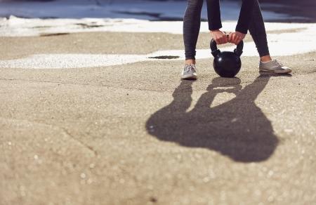 ケトルベルを持ち上げてフィットネス crossfit 女性の影 写真素材