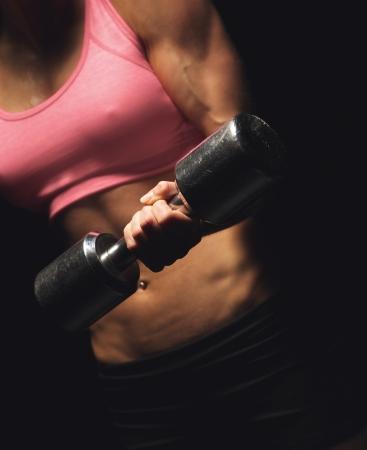 levantamiento de pesas: Torso de un gimnasio activa mujer que hace un entrenamiento de potencia con una mancuerna