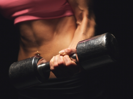 Strong woman's hand lifting a dumbbell photo