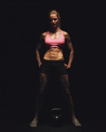 mujer deportista: Longitud total de un fisicoculturista con pesas rusas sobre fondo negro