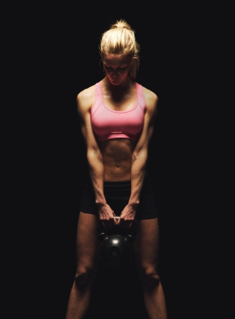 Fitness woman doing a weight training by lifting a heavy kettlebell photo