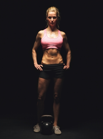Portrait of a strong fitness woman in sportswear standing on black background photo