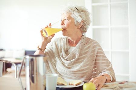 Elderly woman drinking a glass of orange juice Stock Photo