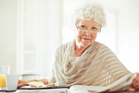 Happy senior woman reading her morning newspaper photo