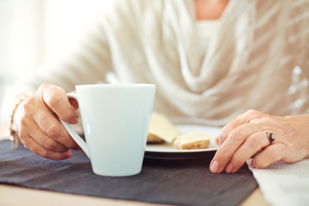 Closeup of a senior woman's hands with a cup of coffee photo