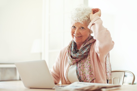 70s adult: Cheerful grandmother sitting at home using her laptop