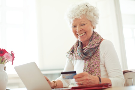 online transaction: Old woman happy doing her shopping online using a credit card
