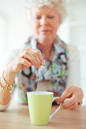 Old lady sitting at home holding and dipping a tea bag photo