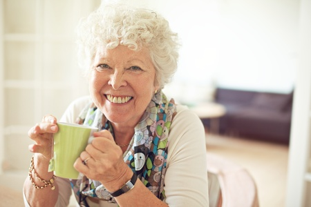 Closeup of a charming old lady drinking her tea photo