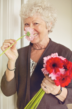 Cheerful senior lady smelling a flower indoors photo
