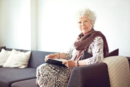 Nonna rilassato seduto sul divano di casa Archivio Fotografico - 20899403