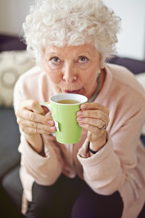 Closeup of a mature lady looking at you while drinking her tea photo
