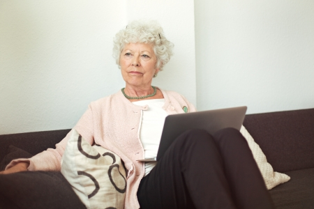 Cheerful senior lady smelling a flower indoors Stock Photo - 20899411