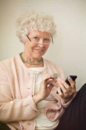 Old lady texting someone using her cell phone Stock Photo - 20899415