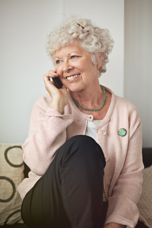 Happy senior woman with a cell phone sitting at home Stock Photo - 20899421