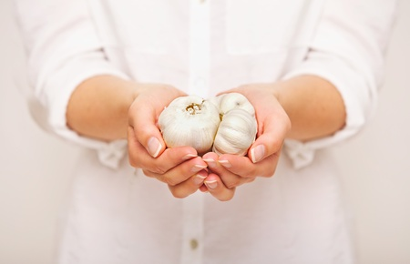 Female holding cloves of garlic in both hands photo
