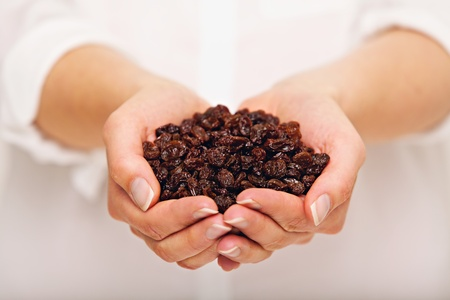 Female holding a handful of raisins Banco de Imagens