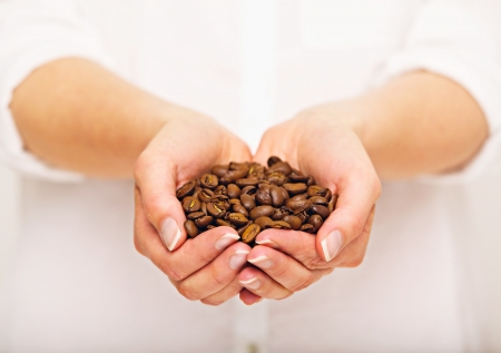 Woman with a handful of coffee beans in both hands photo