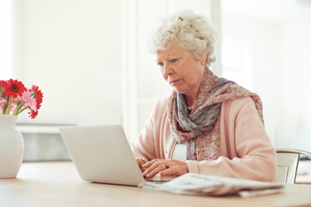 Elderly woman at home typing something using her laptop