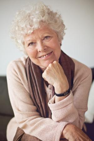 Closeup of a senior woman sitting at home and looking at the camera Stock Photo - 20899510