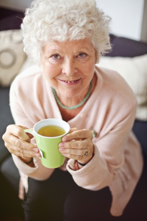 Indoor senior woman enjoying her tea and smiling at you photo