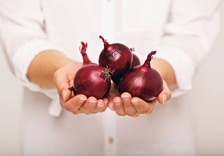 Woman showing red onions in her hands photo