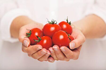 handful: Female with a handful of fresh tomatoes