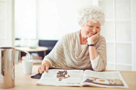 Elegant grandmother sitting at home reading a magazine Stock Photo - 21000367