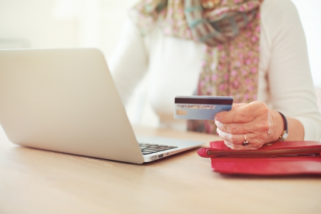 Senior woman's hand holding a credit card while in front of the laptop shopping online Stock Photo - 21000370