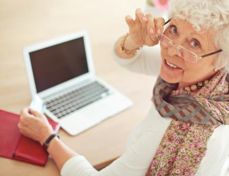 Vieille femme avec carte de crédit en face de son ordinateur portable qui vous regarde Banque d'images - 21000373