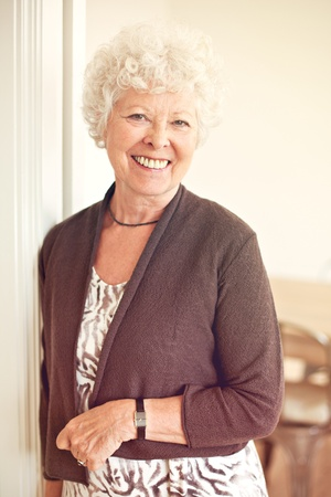 Closeup of a cheerful old woman at home standing Stock Photo - 21000374