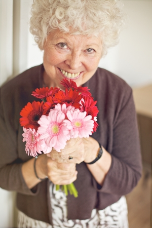 Smiling senior woman holding a bouquet of flowers Stock Photo - 21000377