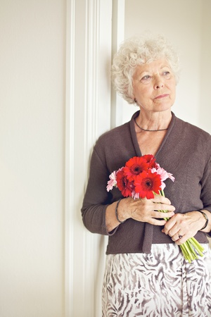 Mature woman holding a bouquet of flowers posing Stock Photo - 21000380