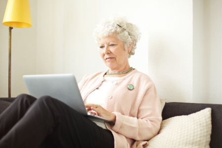 Retired senior woman sitting at home using her laptop Stock Photo - 21000381