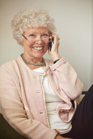 Cheerful woman smiling while calling on her cell phone photo